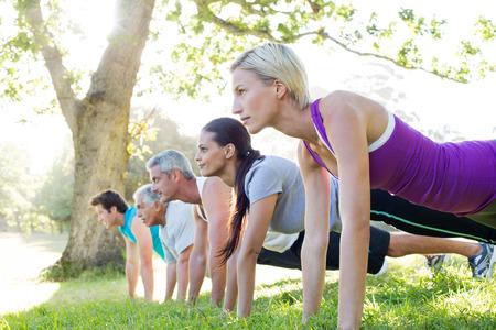 gimnasio mujeres: Formaci�n de grupo atl�tico feliz en un d�a soleado Foto de archivo