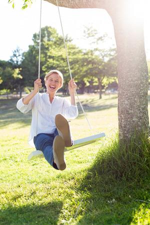 Gelukkig blonde swing op een zonnige dag Stockfoto
