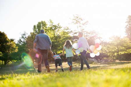 outdoor activities: Happy family walking at the park on a sunny day