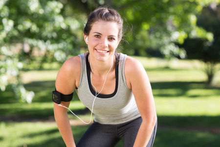 woman working out: Fit brunette on a run in the park on a sunny day Stock Photo