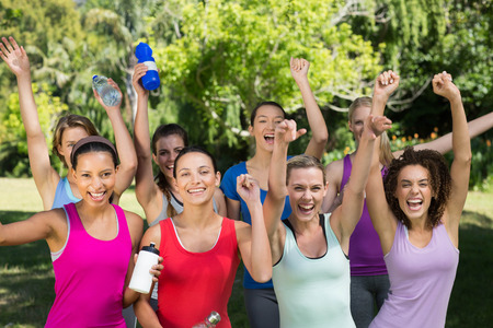 slender woman: Fitness group smiling at camera in park on a sunny day Stock Photo