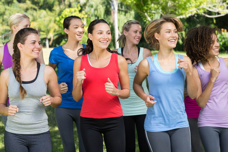mujeres juntas: Fitness group jogging in the park on a sunny day