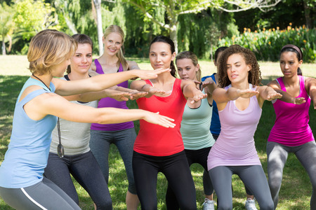 squatting: Fitness group squatting in park on a sunny day Stock Photo