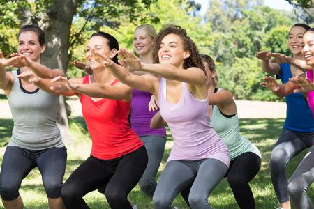cuclillas: Grupo de la aptitud en cuclillas en el parque en un d�a soleado