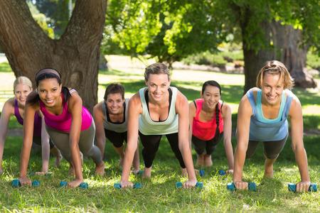 mujeres juntas: Planking grupo de la aptitud en el parque en un día soleado Foto de archivo