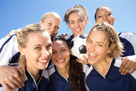 recreational sports: Pretty football players celebrating their win on a sunny day Stock Photo