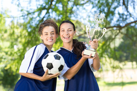 recreational sports: Pretty football players cheering at camera on a sunny day