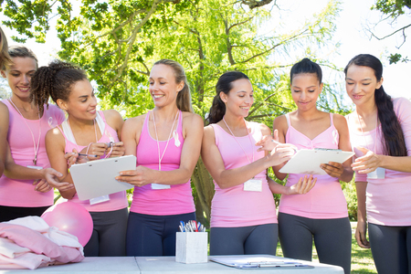 Smiling women organising event for breast cancer awareness on a sunny day
