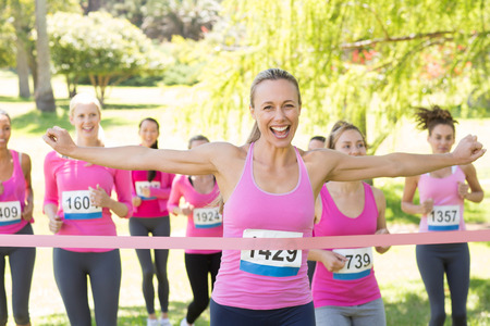 breast cancer: Smiling women running for breast cancer awareness on a sunny day Stock Photo