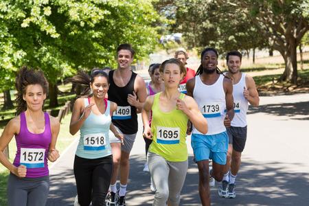 marathon running: Happy people running race in park on a sunny day Stock Photo