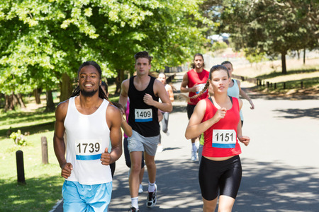 caucasian race: Happy people running race in park on a sunny day Stock Photo