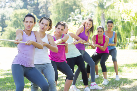 woman rope: Fitness group playing tug of war on a sunny day