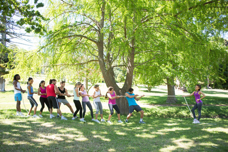 Fitness group playing tug of war on a sunny day photo
