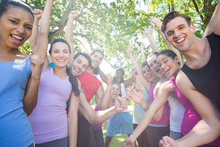 healthy lifestyle: Fitness group cheering at camera in park on a sunny day