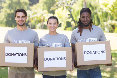 altruismo: Voluntarios felices con cajas de donaci�n en el parque en un d�a soleado