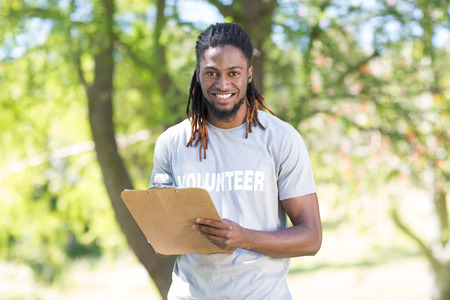 Happy volunteer in the park holding clipboard on a sunny day