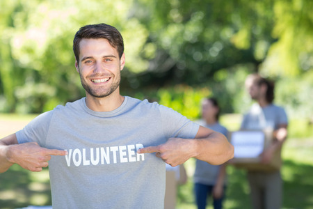volunteerism: Happy volunteer in the park on a sunny day