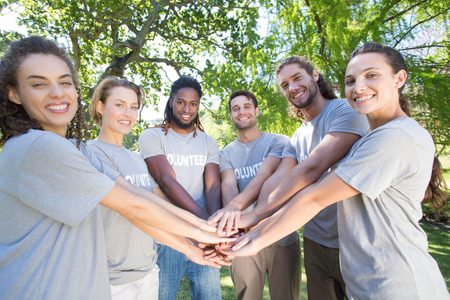 charity work: Happy volunteers in the park on a sunny day