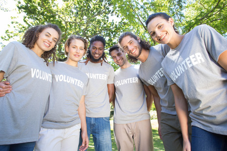 selfless: Happy volunteers in the park on a sunny day