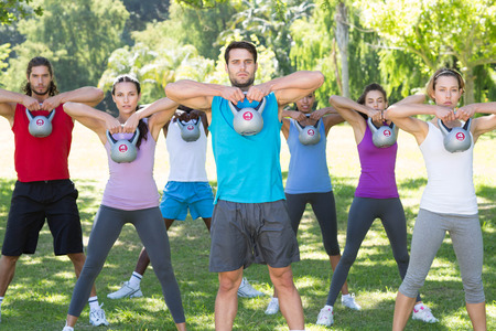 Fitness group working out in park with kettle bells  on a sunny day Stock Photo