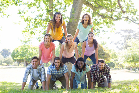 human pyramid: Happy friends in the park making human pyramid on a sunny day Stock Photo