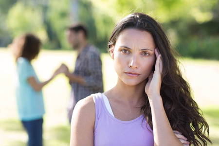 crush on: Woman upset at her crush with other girl on a sunny day Stock Photo