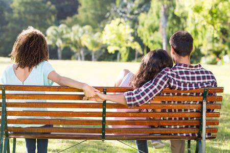 hombre solo: Mujer sola que se sienta con la pareja en el parque en un d�a soleado