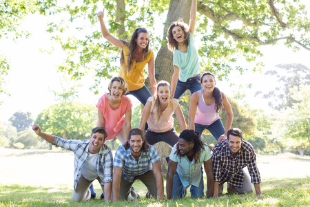 al aire libre: Amigos felices en el parque haciendo pirámide humana en un día soleado