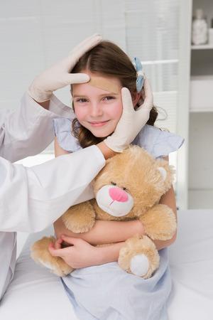 Doctor making plaster in little girl in medical office photo