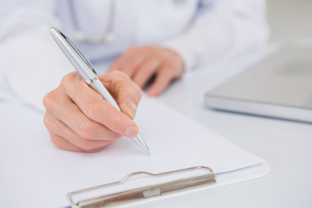 Doctor writing on a clipboard in medical office Stock Photo