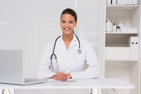 doctor writing: Brunette doctor writing on clipboard in medical office Stock Photo