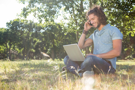 Young man using laptop in the park on a summers day photo