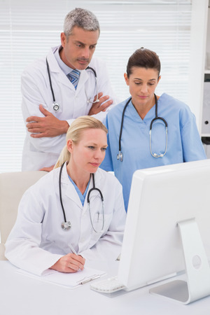 Doctors looking at computer in medical office photo