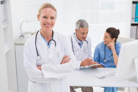 looking at camera: Smiling doctor looking at camera in medical office