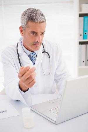 prescriptions: M�dico escribiendo en el teclado las recetas en el consultorio m�dico