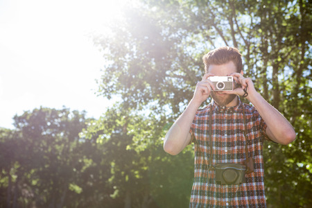 summers: Handsome hipster using vintage camera on a summers day