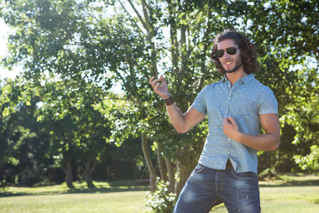 air guitar: Young man playing air guitar in the park on a summers day