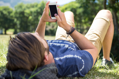 typing man: Handsome hipster using phone in park on a summers day