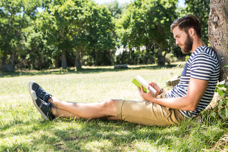 young tree: Hipster reading a book in the park on a summers day Stock Photo