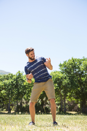 air guitar: Handsome hipster playing air guitar on a summers day Stock Photo