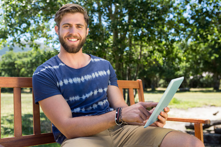 green man: Young man using tablet on park bench on a summers day