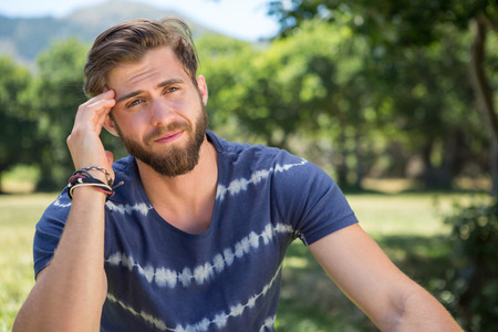 wincing: Handsome hipster getting a headache on a summers day