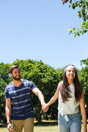 Hipster couple walking in the park on a summers day photo