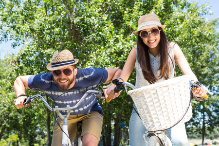 couple nature: Hipster couple on a bike ride in the park on a summers day Stock Photo