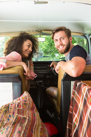 Hipster couple driving in camper van on a summers day photo