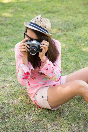 summers: Pretty brunette with retro camera on a summers day