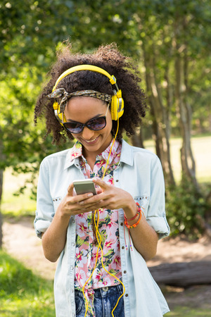 hairband: Pretty hipster using her smartphone on a summers day
