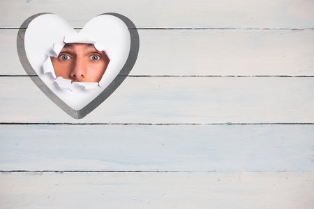 paper rip: Young man looking through paper rip against heart in wood Stock Photo