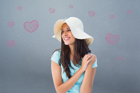 sunhat: Happy young brunette wearing sunhat against grey