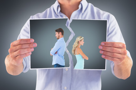 Unhappy couple not speaking to each other  against grey vignette photo